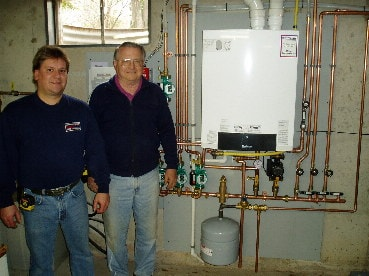 Hannabery HVAC installation mechanic and Mr. McClure standing next to his new Buderus side-wall vented Boiler with a 50-gallon Indirect Hot Water Tank.